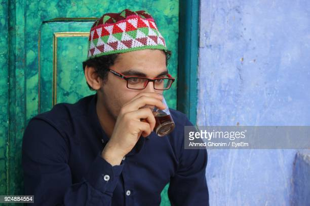 Close-Up Of Young Man Drinking Tea Against Wall