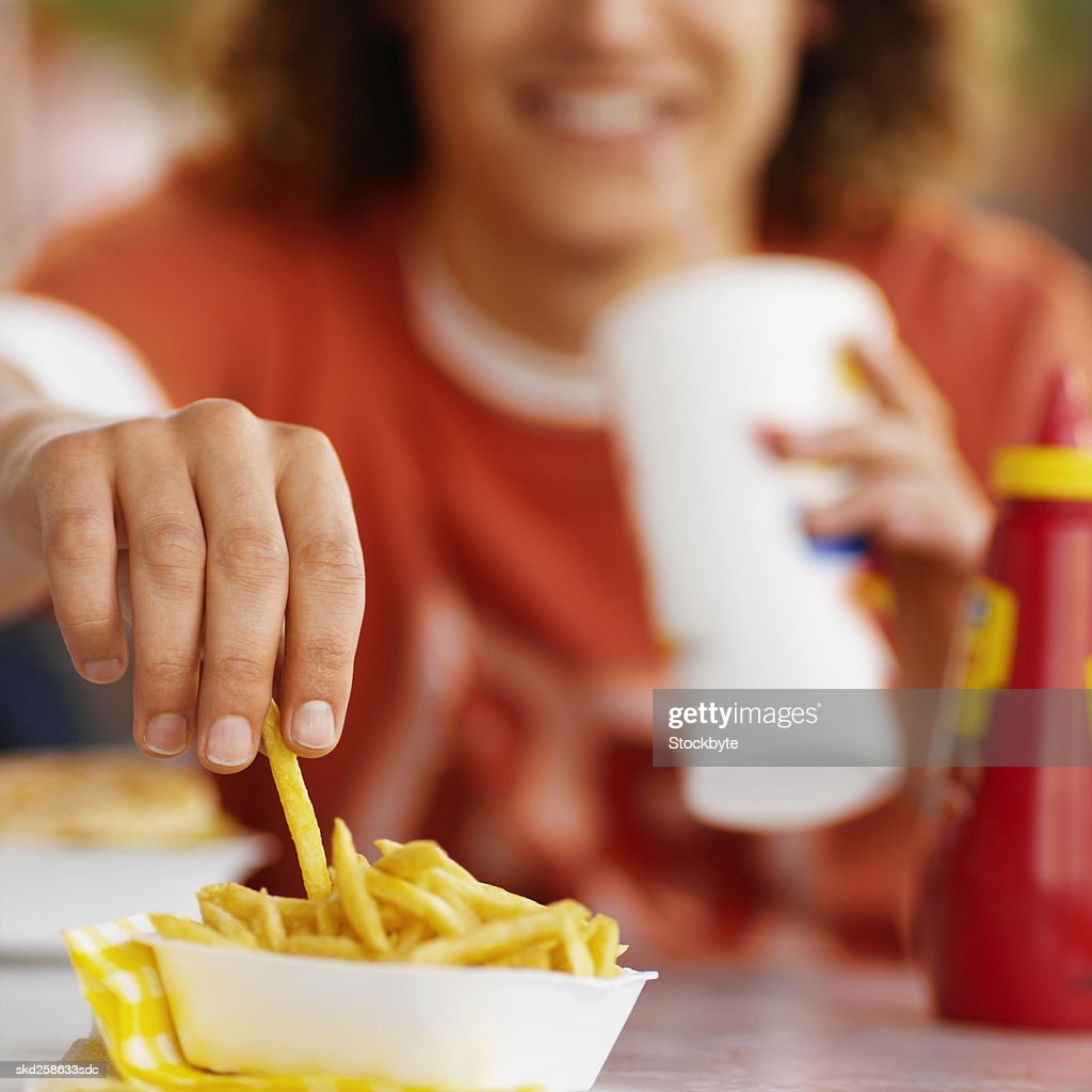 Close-up of young man eating in fast food restaurant : Stock Photo