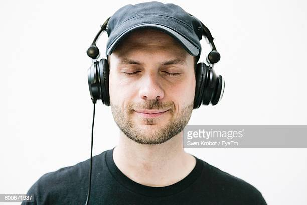 Close-Up Of Young Man Enjoying Music With Headphones Against White Background