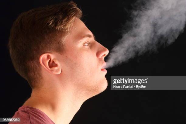 Close-Up Of Young Man Exhaling Smoke Against Black Background