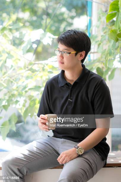 close-up of young man holding drink while sitting on retaining wall - woman sitting on man's lap stock pictures, royalty-free photos & images