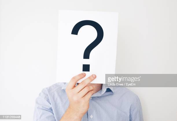 close-up of young man holding question mark sign while standing against white background - mystery stock pictures, royalty-free photos & images