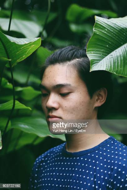 Close-Up Of Young Man Looking Away While Standing By Plants At Park