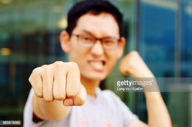 close-up of young man punching in city - fighting stance stock pictures, royalty-free photos & images