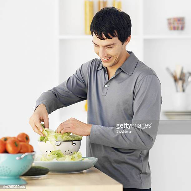 Close-up of young man putting lettuce in dish