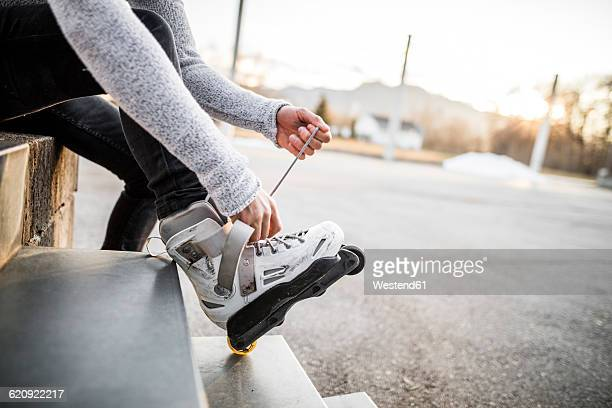close-up of young man putting on inline skates - inline skate stock photos and pictures