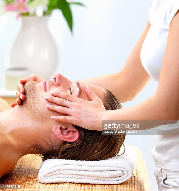 Nahaufnahme des jungen Mannes empfangen Gesichtsmassage im day spa