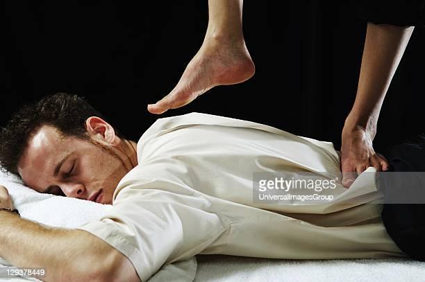 Closeup of young man receiving foot back massage