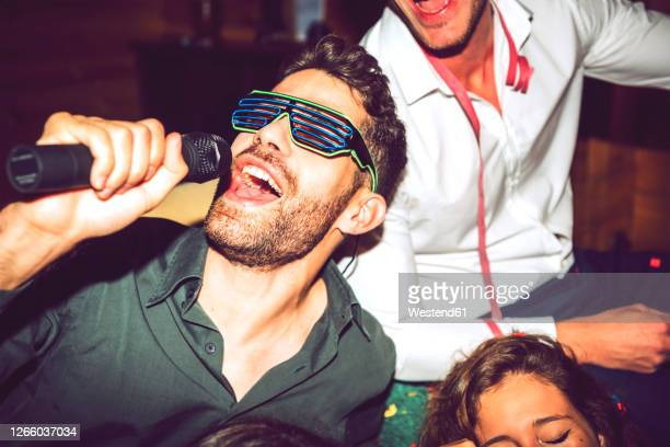 close-up of young man singing karaoke while enjoying with friends in party - karaoke stock pictures, royalty-free photos & images