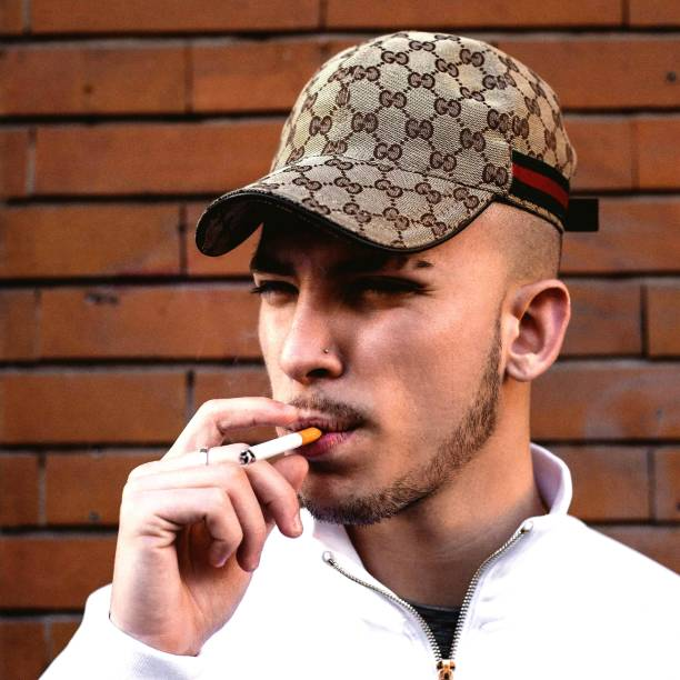 Close-Up Of Young Man Smoking Cigarette Against Brick Wall