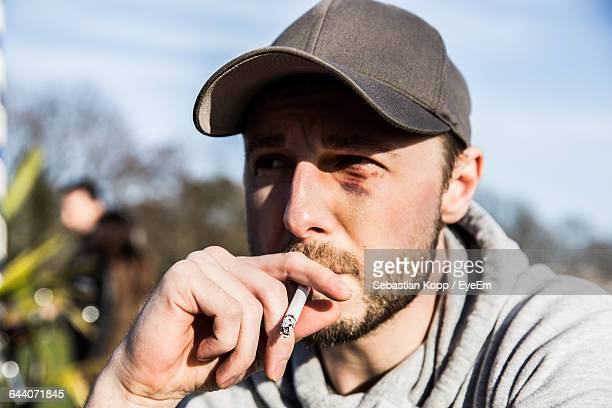 close-up of young man smoking cigarette outdoors - black eye stock pictures, royalty-free photos & images