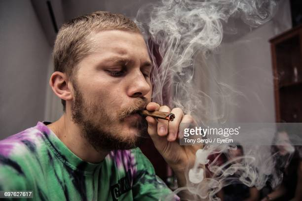 Close-Up Of Young Man Smoking Marijuana Joint