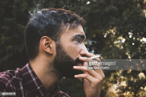 close-up of young man smoking outdoors - smoking issues stock pictures, royalty-free photos & images