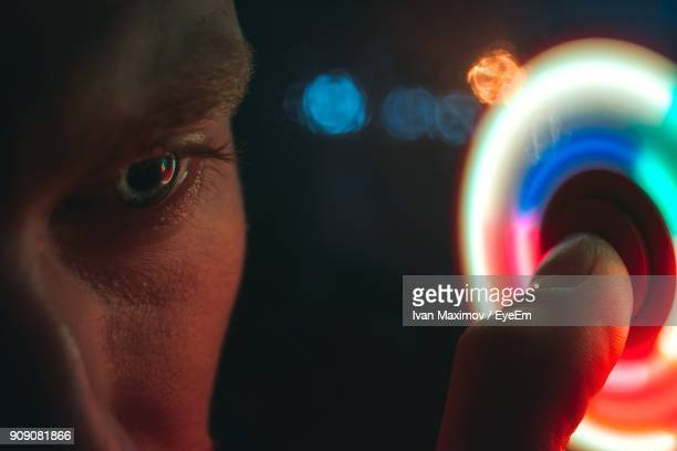 Close-Up Of Young Man Spinning Illuminated Fidget Spinner At Night