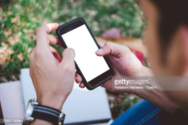 close-up of young man using mobile phone at park - looking over shoulder stock pictures, royalty-free photos & images