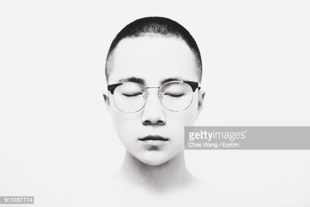 Close-Up Of Young Man Wearing Eyeglasses With Eyes Closed Against White Background