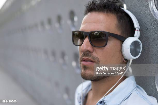 Close-Up Of Young Man Wearing Sunglasses Listening Music Through Headphones