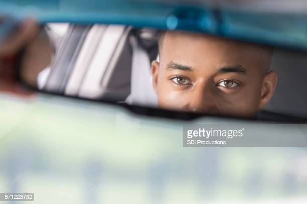 Closeup of young man's reflection in rear view mirror