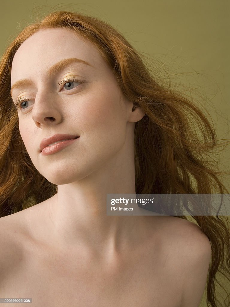 closeup of young naked woman with long ginger hair looking aside