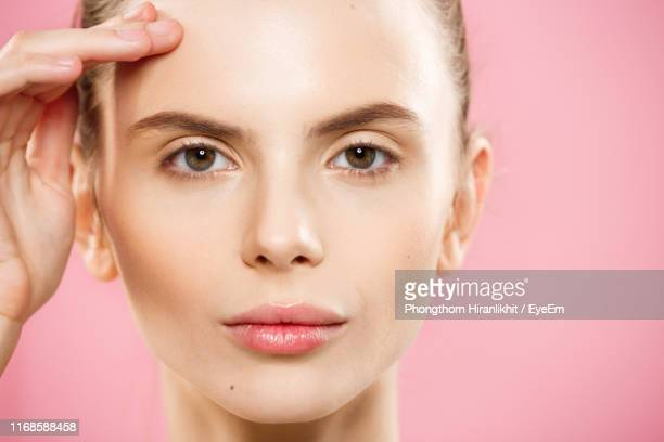 close-up of young woman against pink background - one young woman only stock pictures, royalty-free photos & images