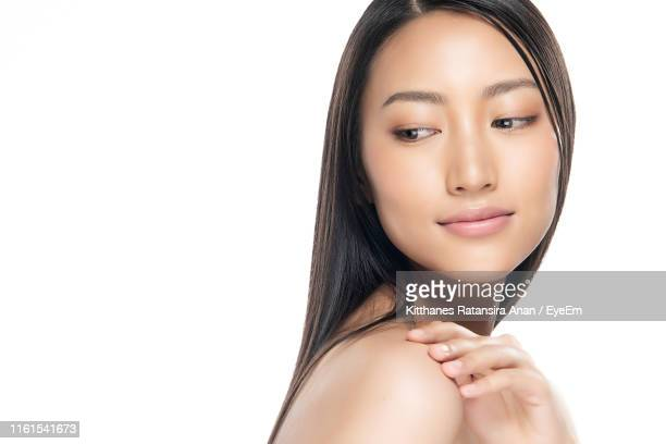 close-up of young woman against white background - halbbekleidet stock-fotos und bilder