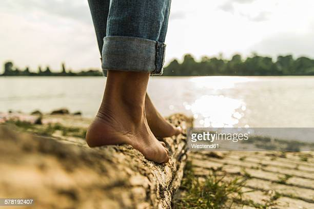 Close-up of young woman balancing on log by the riverside