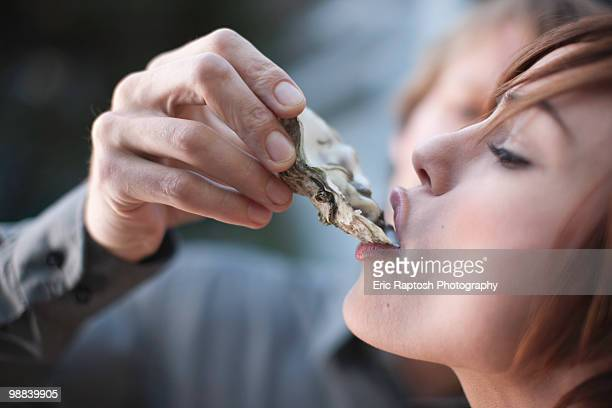 Close-up of young woman being fed an oyster.