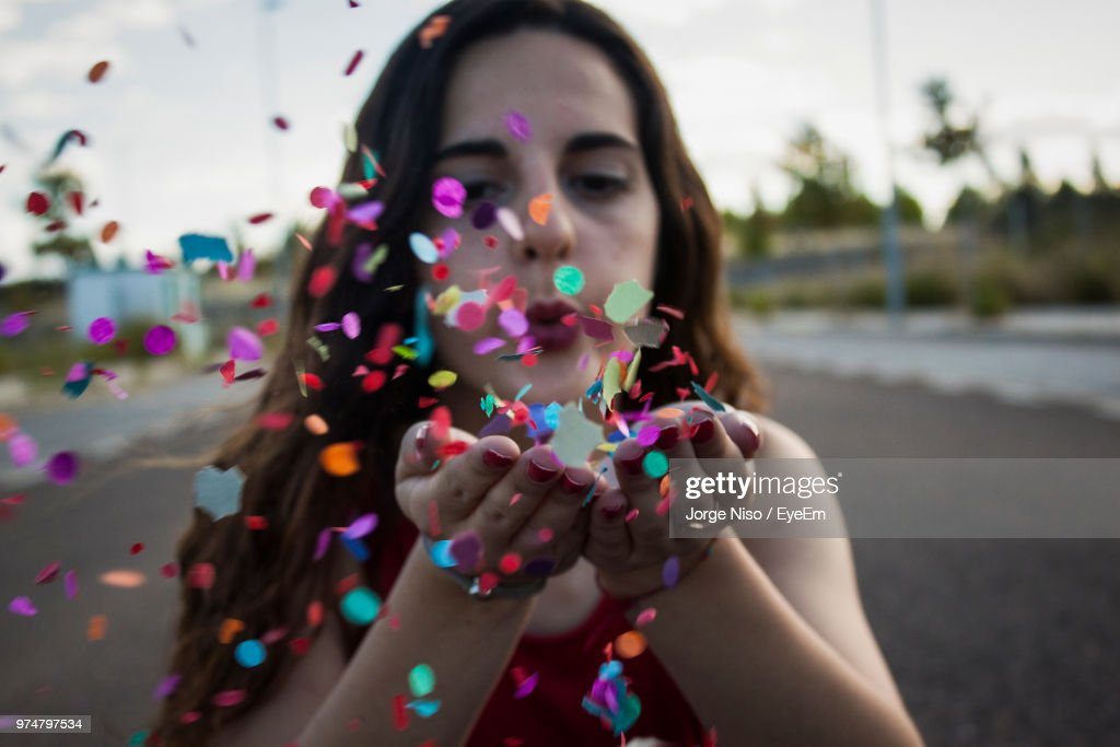 Close-Up Of Young Woman Blowing Confetti On Road : Stock Photo
