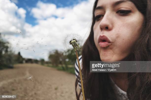 close-up of young woman blowing dandelion seeds against sky - fragility stock pictures, royalty-free photos & images