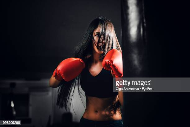 Close-Up Of Young Woman Boxing In Darkroom