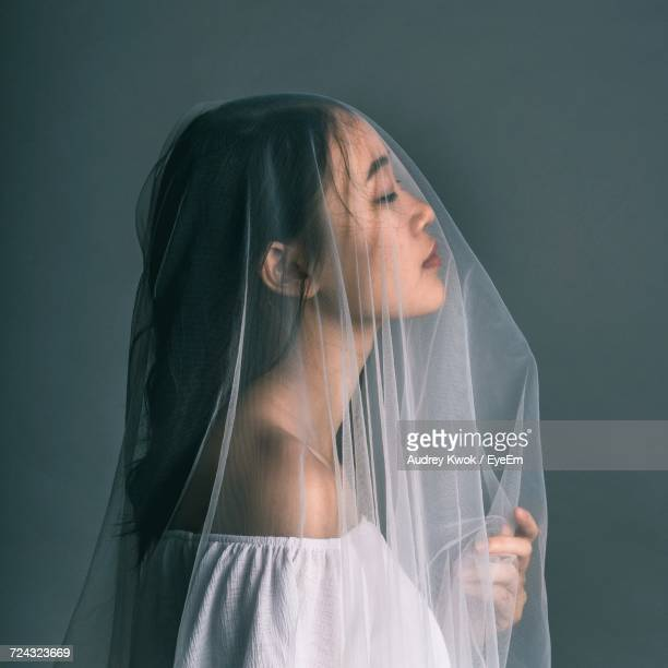 close-up of young woman covering face - veil stock photos and pictures