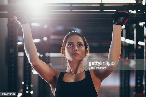 close-up of young woman doing chin-ups at gym - chin ups stock photos and pictures