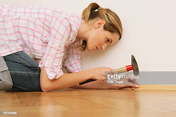 close-up of young woman doing home improvement with hammer and nail