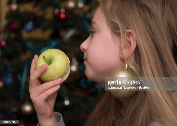 Close-Up Of Young Woman Eating Green Apple