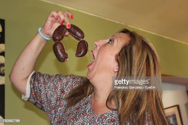 Close-Up Of Young Woman Eating Sausage