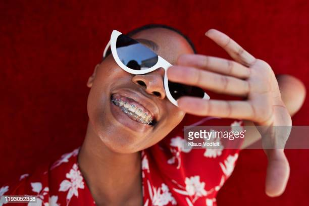 close-up of young woman gesturing against red wall - parte del cuerpo humano fotografías e imágenes de stock
