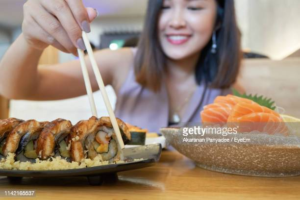 close-up of young woman having food at table in restaurant - 盛り付け ストックフォトと画像
