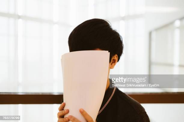 close-up of young woman hiding face with papers at office - se cacher photos et images de collection