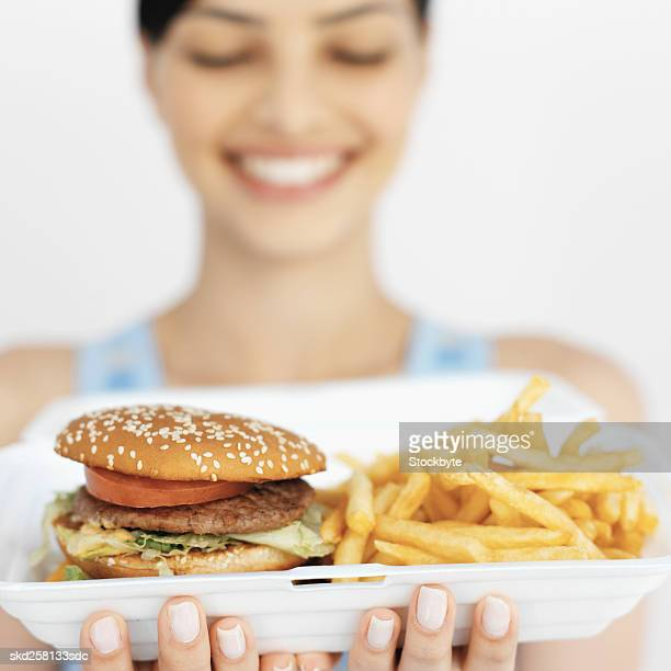 Close-up of young woman holding carton of French fries and burger