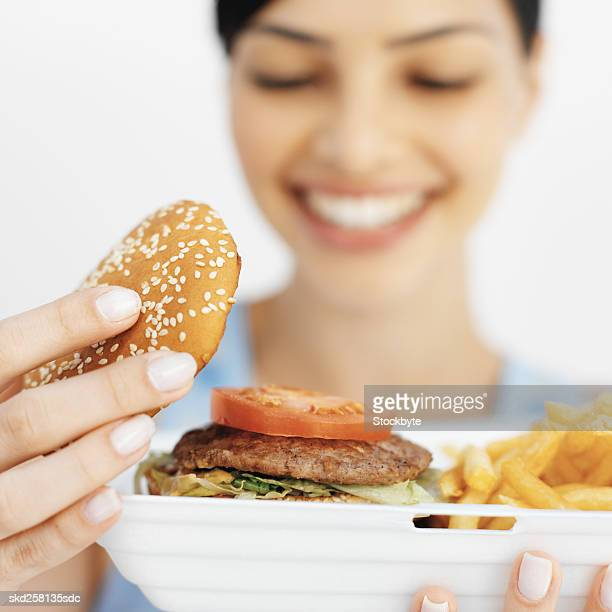 Close-up of young woman holding carton of French fries and lifting bun off burger