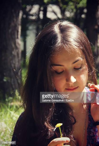 Close-Up Of Young Woman Holding Flower On Sunny Day