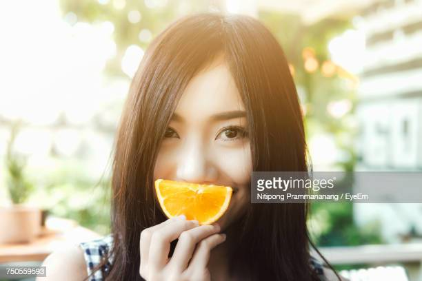 Close-Up Of Young Woman Holding Fruit