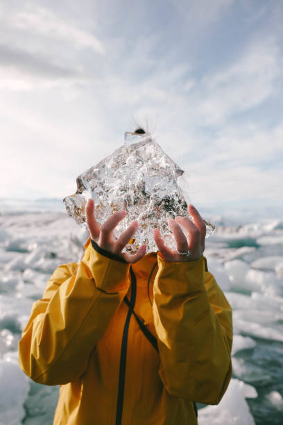 Close-Up Of Young Woman Holding Ice Against Sea