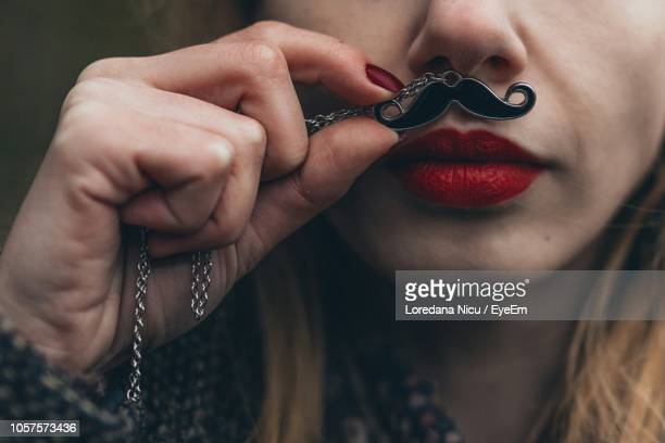Close-Up Of Young Woman Holding Mustache Pattern Pendant