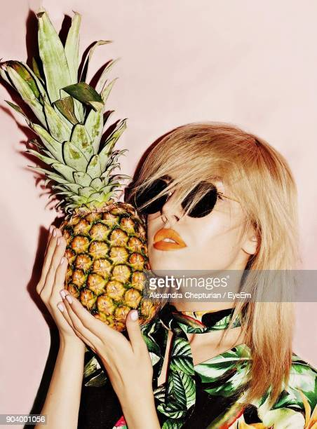 Close-Up Of Young Woman Holding Pineapple Against Colored Background
