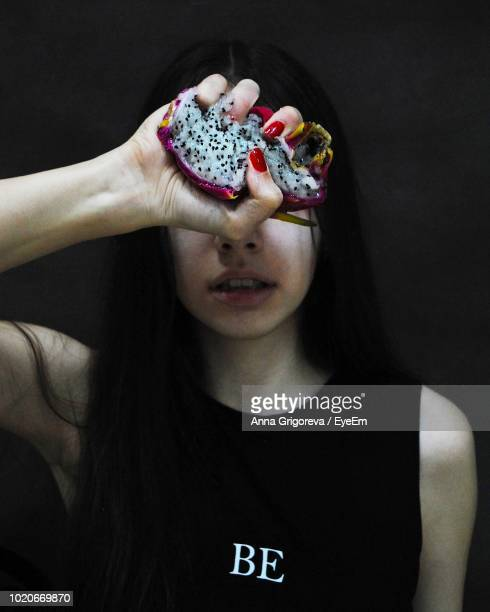 Close-Up Of Young Woman Holding Pitaya Against Black Background