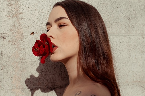 Close-Up Of Young Woman Holding Rose Against Wall - gettyimageskorea