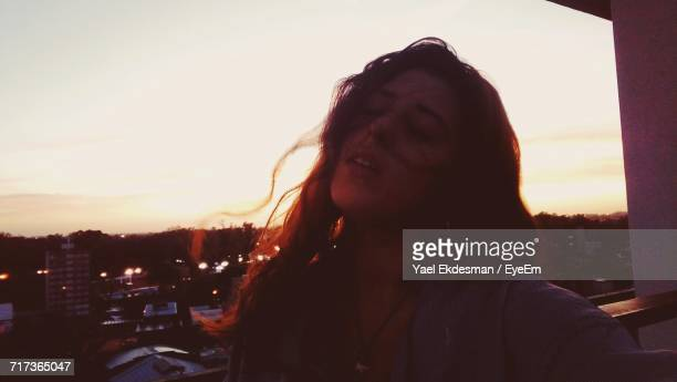 Close-Up Of Young Woman In Balcony Against Sky During Sunset