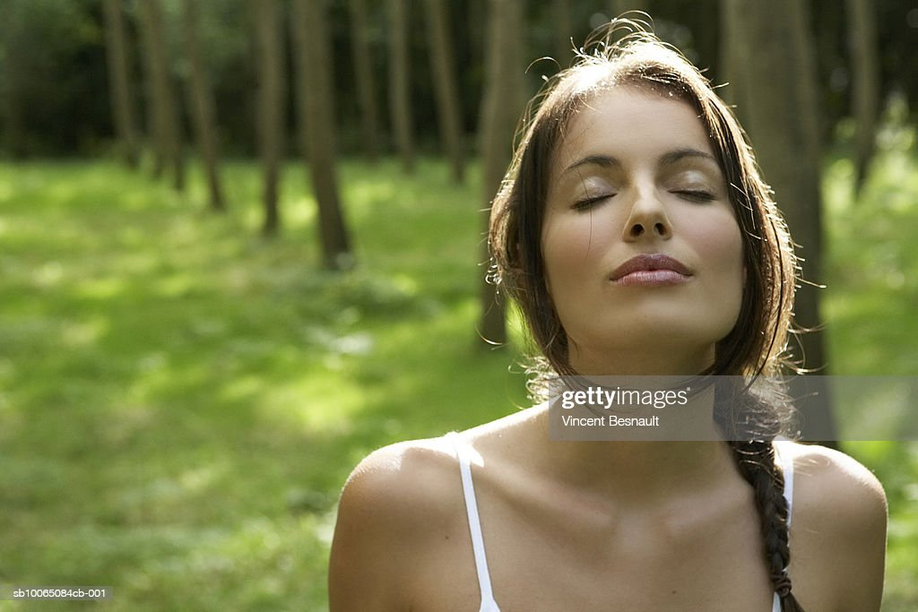 Close-up of young woman in forest, eyes closed : Stock Photo