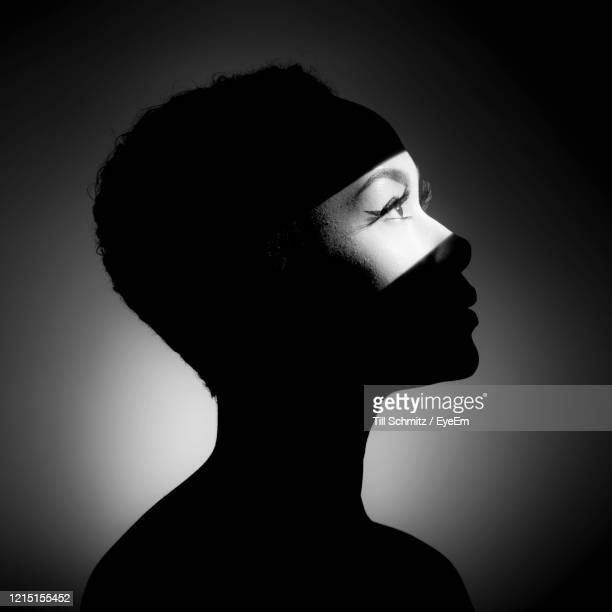 close-up of young woman in light against black background - profile stock pictures, royalty-free photos & images